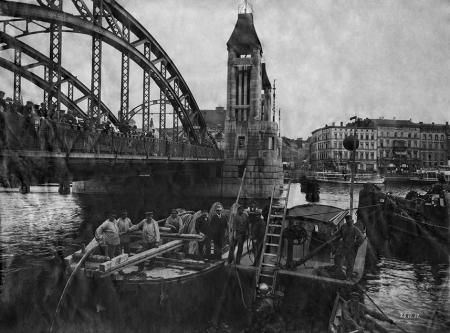 Na tej fotografii zarejestrowano prace związane z przekładaniem kabla na dnie Odry, ta skomplikowana operacja wzbudziła duże zainteresowanie szczecinian licznie zgromadzonych na Moście Kłodnym. W tle po prawej stronie wyraźnie widoczne są kamienice przy narożniku ul. Lazurowej, ku której skierowany został wylot nowego Mostu Kłodnego w konstrukcji stalowej – wcześniejszy, drewniany most zlokalizowany był w przedłużeniu ul. Kłodnej. (MNS/R-356)