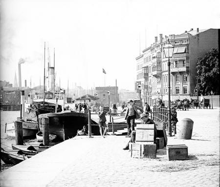 Dzieci i dorożki czekające na podróżnych przy Nabrzeżu Statków Parowych i widok na kamienice przy narożniku ul. Lazurowej; na jej zamknięciu do czasu budowy nowego Mostu Kłodnego stał pawilon urzędu locji, w którym aktualizowano oznakowanie nawigacyjne. (MNS/A.Foto/15689)