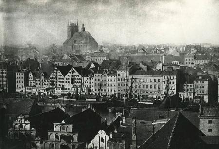 Jedna z najstarszych fotograficznych panoram Szczecina z dachami spichlerzy na wschodnim brzegu Odry i zabudową nabrzeża zachodniego z masywną bryłą kościoła św. Jakuba, którego wieża w latach 70-tych XIX wieku niewiele różniła się od kształtu sprzed rekonstrukcji hełmu w 2008 roku. (MNS/A.Foto/13648)
