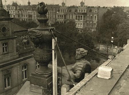 Fotografia ukazuje z bliska dekorację tympanonu dawnego pałacu Stanów Pomorskich przy ul. Staromłyńskiej, pozwala również zobaczyć niezachowane kamienice przy pl. Żołnierza. (MNS/A.Foto/15599)