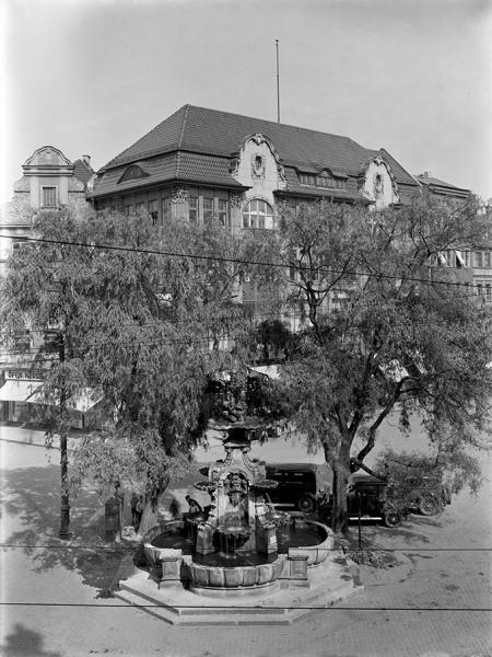 Plac Orła Białego z efektownymi budynkami, które stały przed wojną na miejscu dzisiejszego zespołu gastronomiczno-usługowego; na pierwszym planie otoczona drzewami późnobarokowa fontanna z orłem. (MNS/A.Foto/5013)